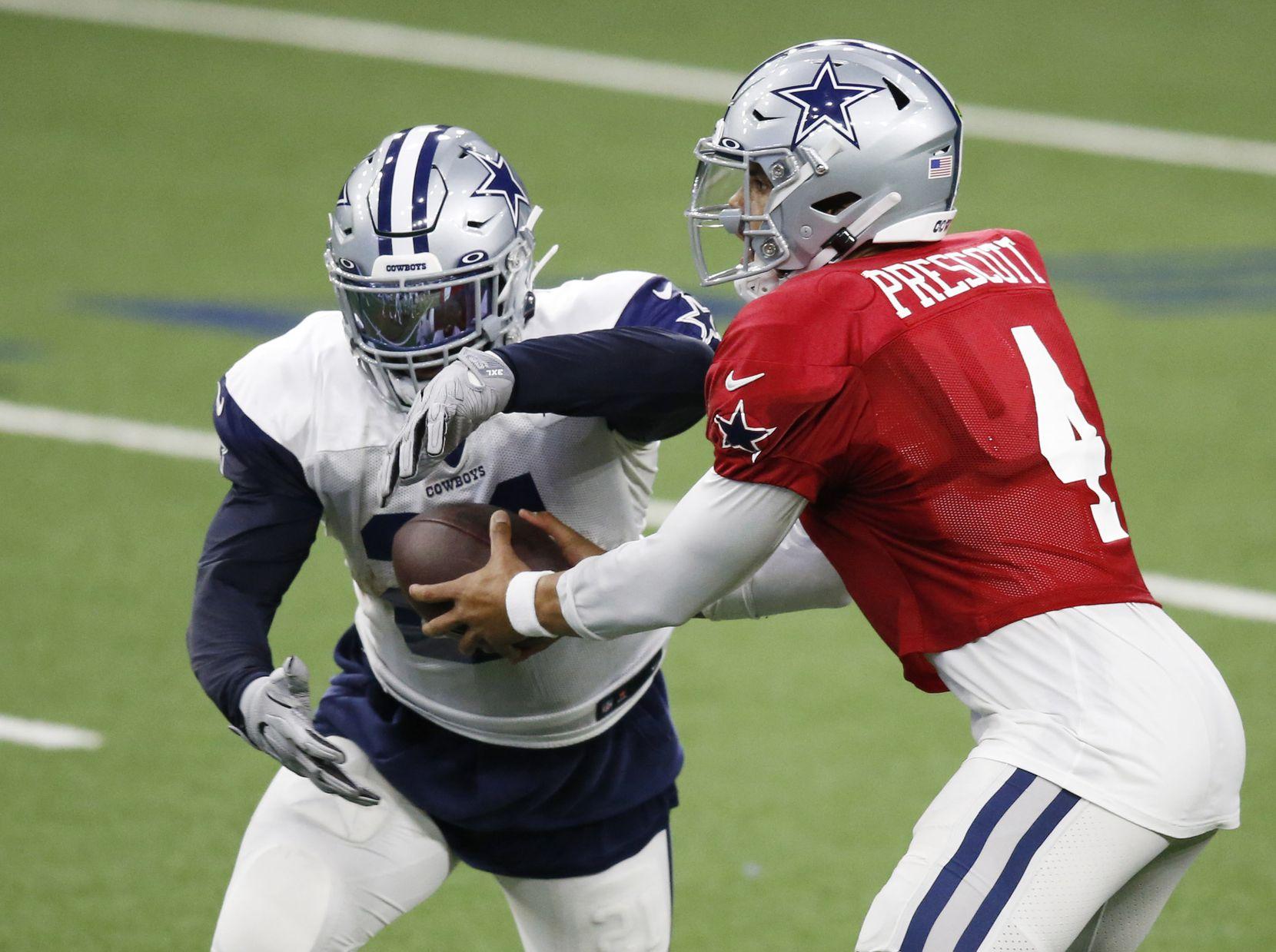 Dallas Cowboys quarterback Dak Prescott (4) hands the ball off to Dallas Cowboys running back Ezekiel Elliott (21) during training camp at the Dallas Cowboys headquarters at The Star in Frisco, Texas on Thursday, August 27, 2020. (Vernon Bryant/The Dallas Morning News)
