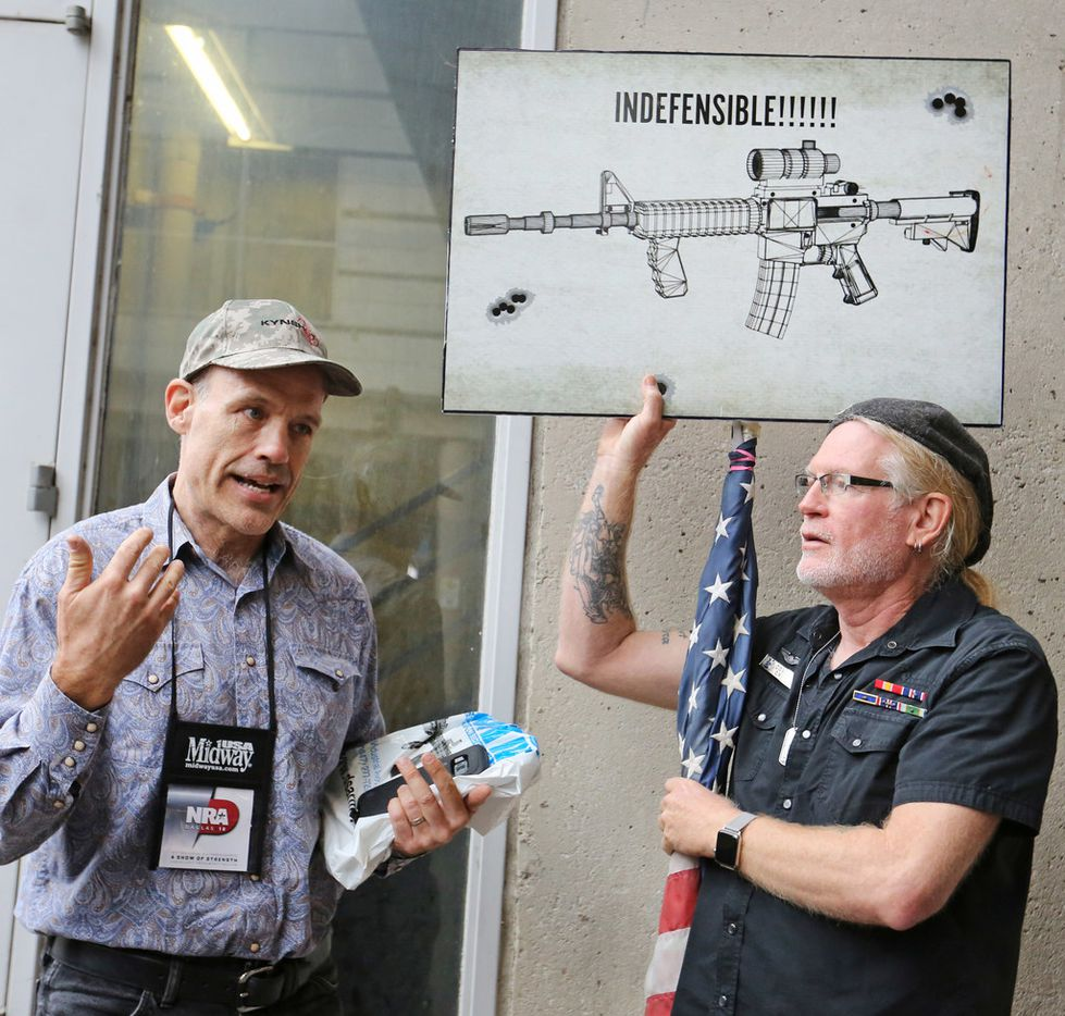 Jim Whalen of West Palm Beach, Fla., a gun proponent, talked civilly with protester David Lyles of Dallas outside the convention center Friday.