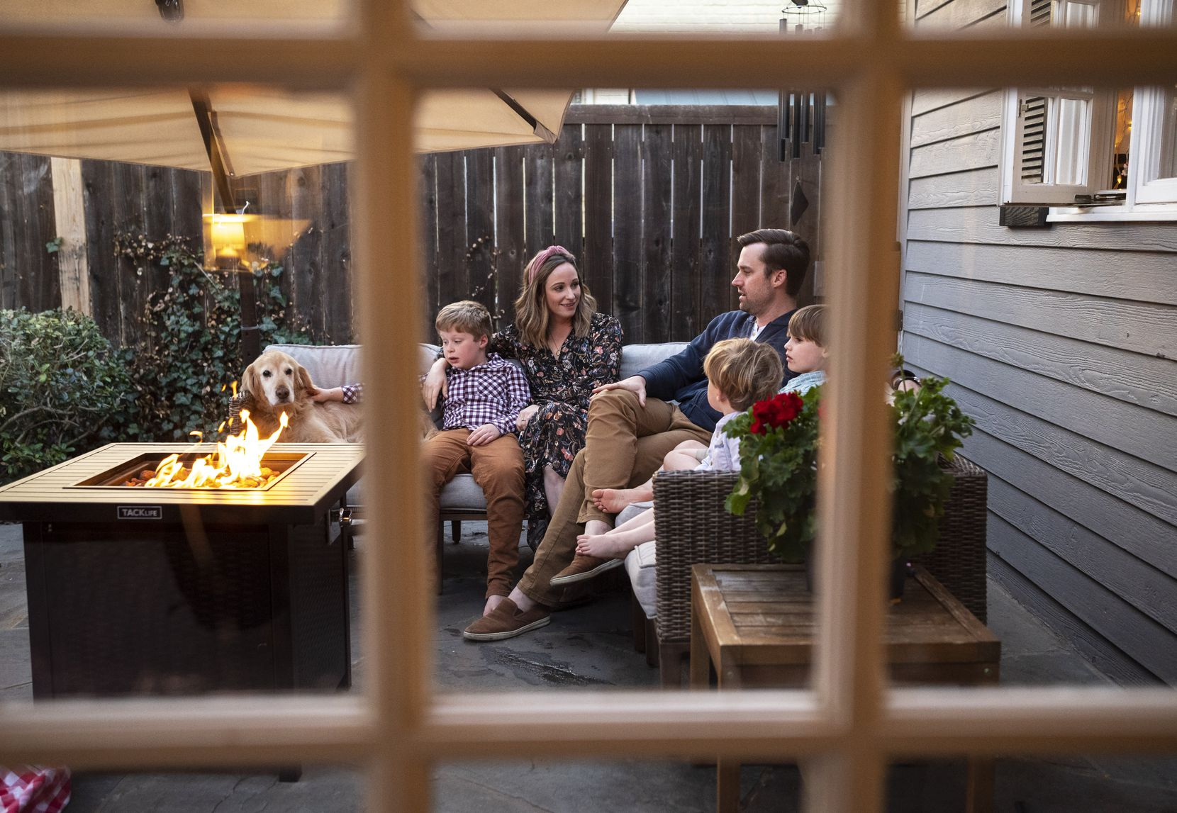 Jessica Barfield, left, and her husband Blake Barfield, with their sons, Henry, 7, left, Wade, 6, and Brooks, 2, far-right, in the backyard porch of their home in Dallas, on Monday, March 08, 2021. The Barfields ate many meals in the back yard to get their three sons outside of the house after spending so much time indoors at the start of the pandemic. The Barfields would also leave their groceries out on the front porch to air out before wiping them down or washing.