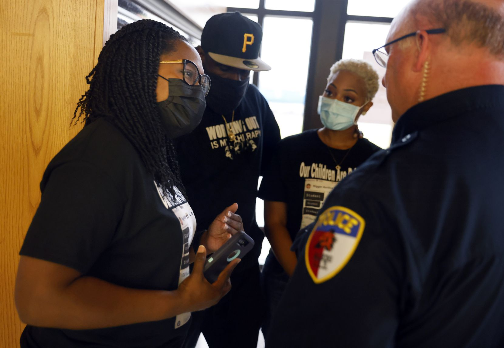 Mothers Tamara Lawrence (left) and Mioshi Johnson visited with Aledo ISD Police Chief Fred Collie after a Thursday night school board meeting in which they raised concerns about the district's reaction to a racist bullying incident that targeted their sons.