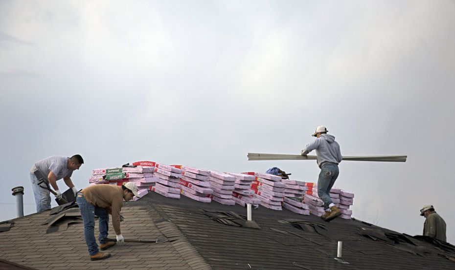 Roofers work on a home in Glenn Heights. (2016 File Photo/The Dallas Morning News)