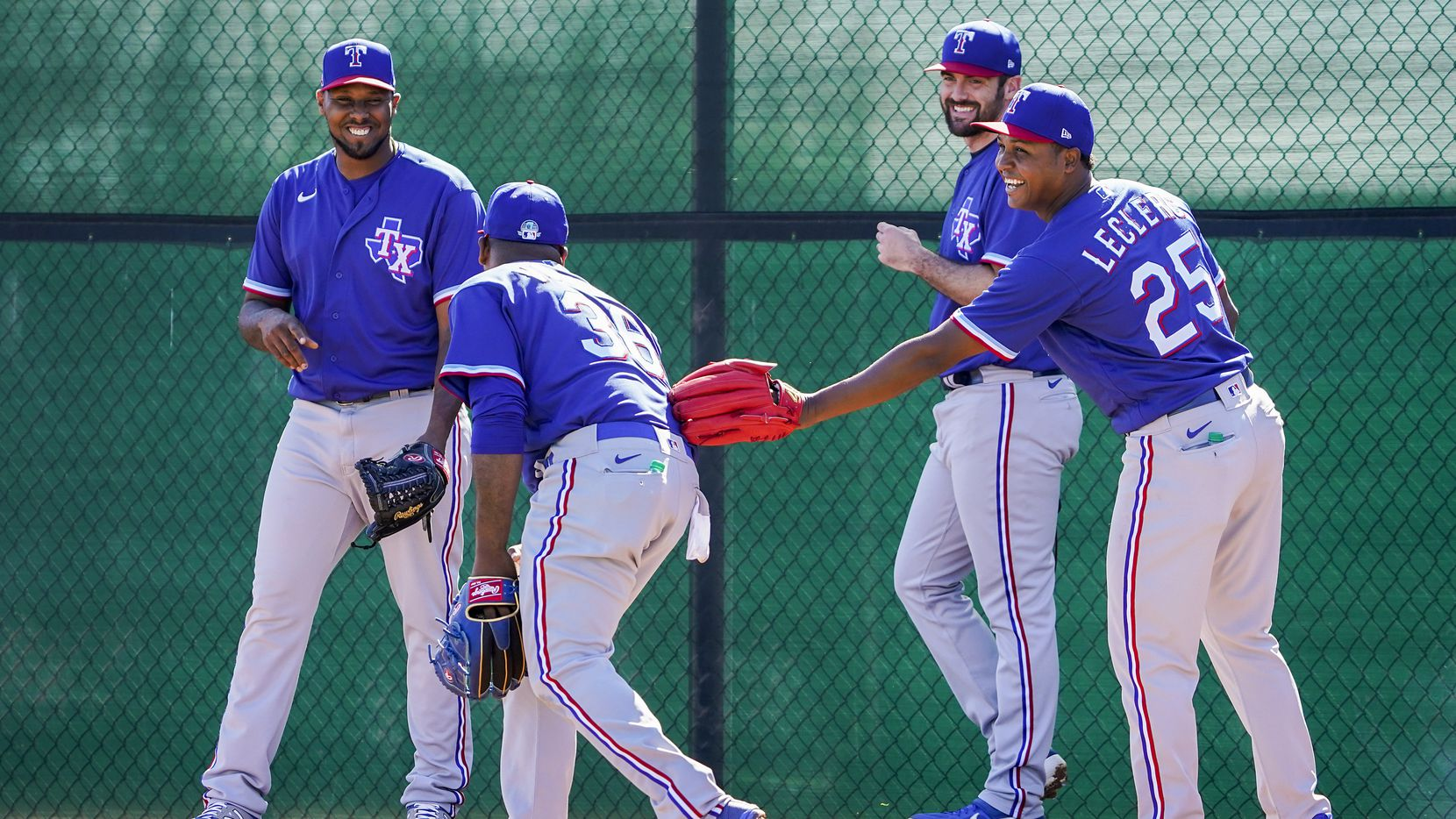 Texas Rangers pitcher Jose Leclerc (right) laughs with Edinson Volquez (36) Juan Nicasio (left) and Brian Flynn as they participate in a fielding drill during a spring training workout at the team's training facility on Saturday, Feb. 15, 2020, in Surprise, Ariz.
