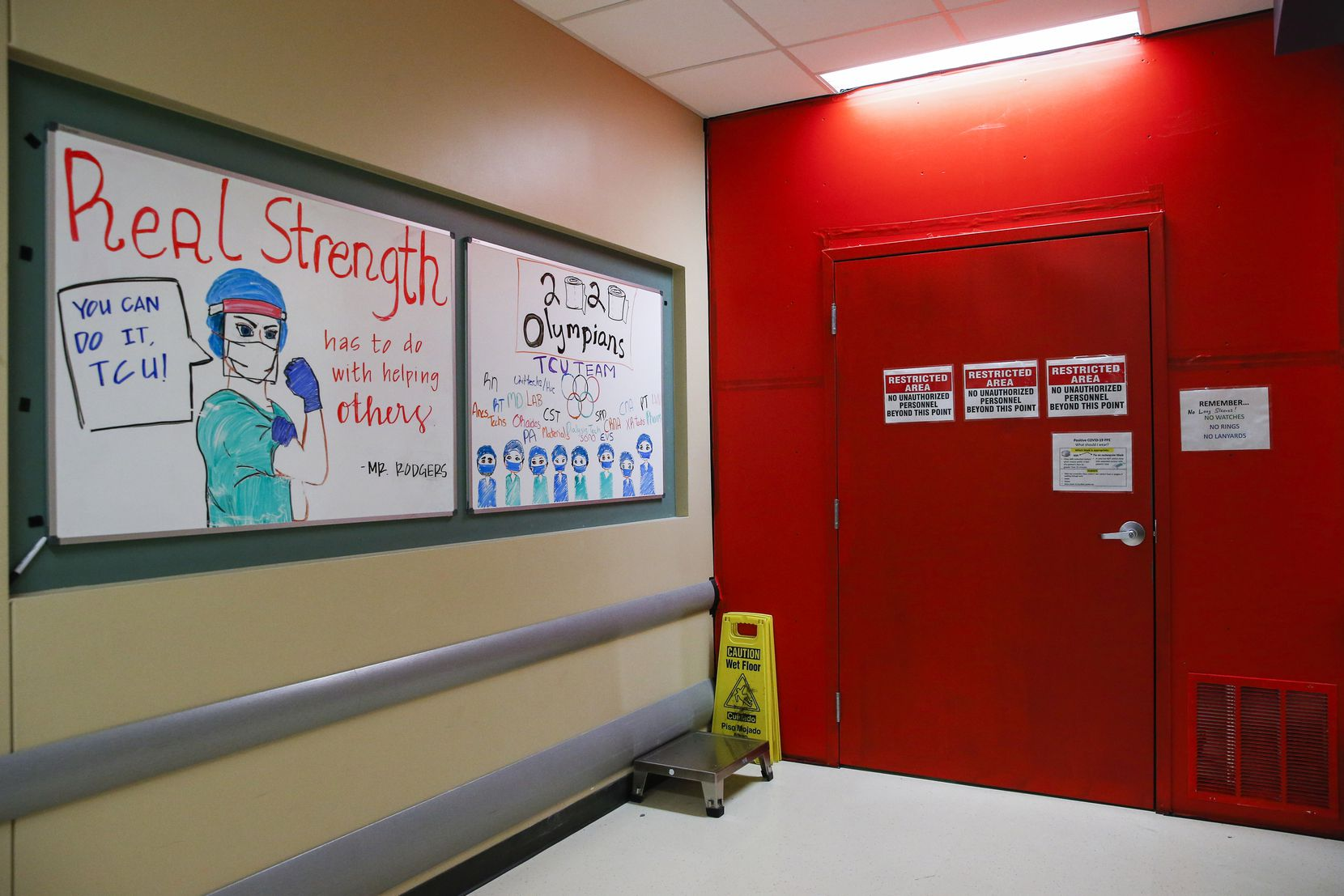 """Supportive signs line the wall adjacent to one of the two entrances to Parkland's Tactical Care Unit, nicknamed the """"red box,"""" On the other side of the door is a sterile space where caregivers don their PPE."""
