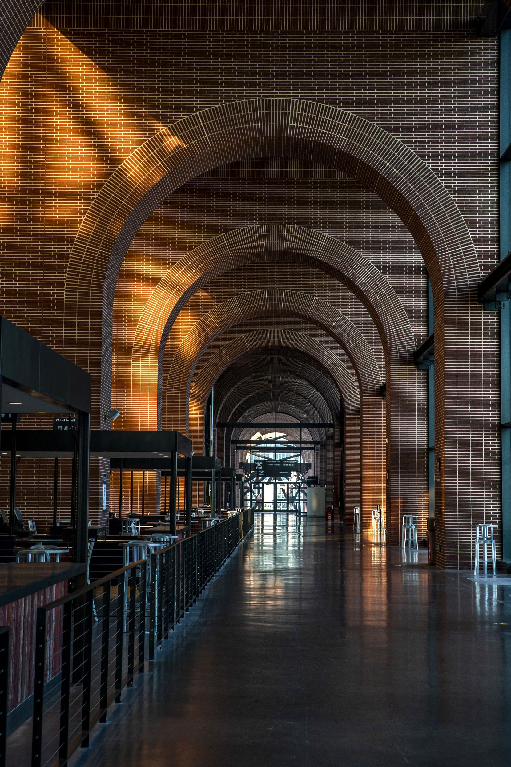 A defining architectural feature of the ballpark is its towering, glass-enclosed arcade of red brick arches.
