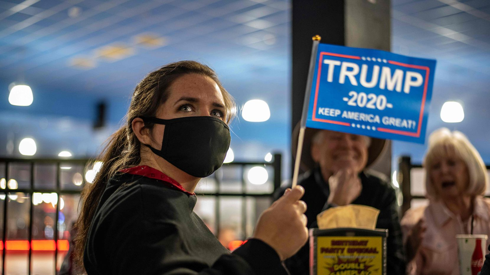 An attendee at a watch party for Republicans waves a Trump 2020 flag on election day, November 3, 2020 in Austin, Texas.