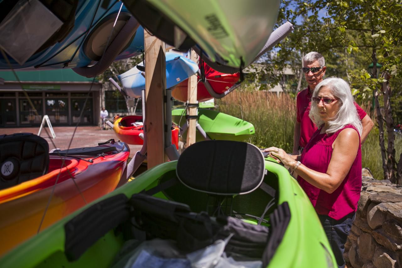 Marie and John Koski admire some new kayaks at L.L. Bean while on vacation in Freeport, Maine. The Koskis are part of a growing group of vacationers 50 and older who are finding creative ways to travel economically.