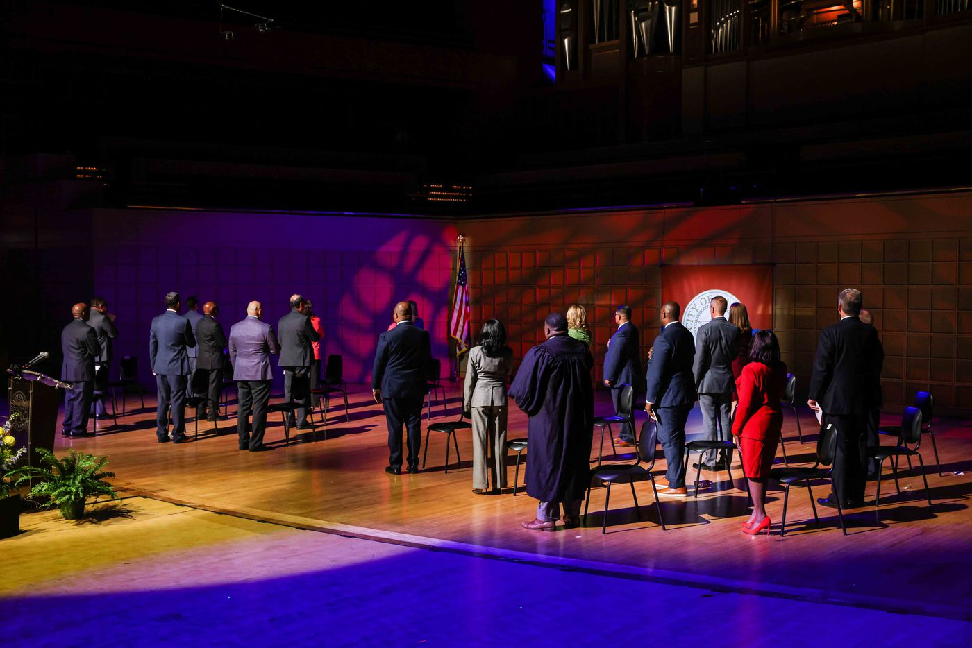 Dallas City Council face the U.S. flag as the national anthem plays during the Inauguration Ceremony at the Meyerson Symphony Center in Dallas on Monday, June 14, 2021. (Lola Gomez/The Dallas Morning News)