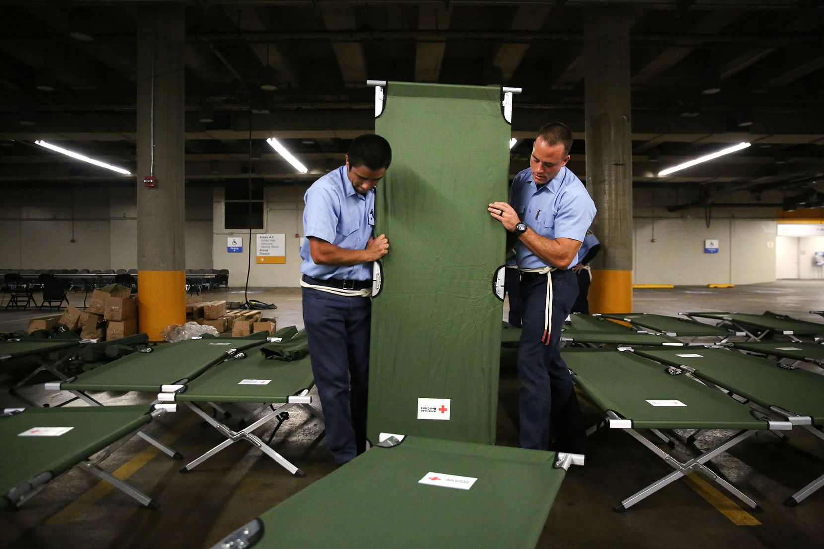"""Dallas Fire-Rescue recruits Marco Huerta (left) and Nathan Johnson help set up beds to house up to 5,000 Gulf Coast residents inside the """"mega shelter"""" at the Kay Bailey Hutchison Convention Center in Dallas on Monday, Aug. 28, 2017."""