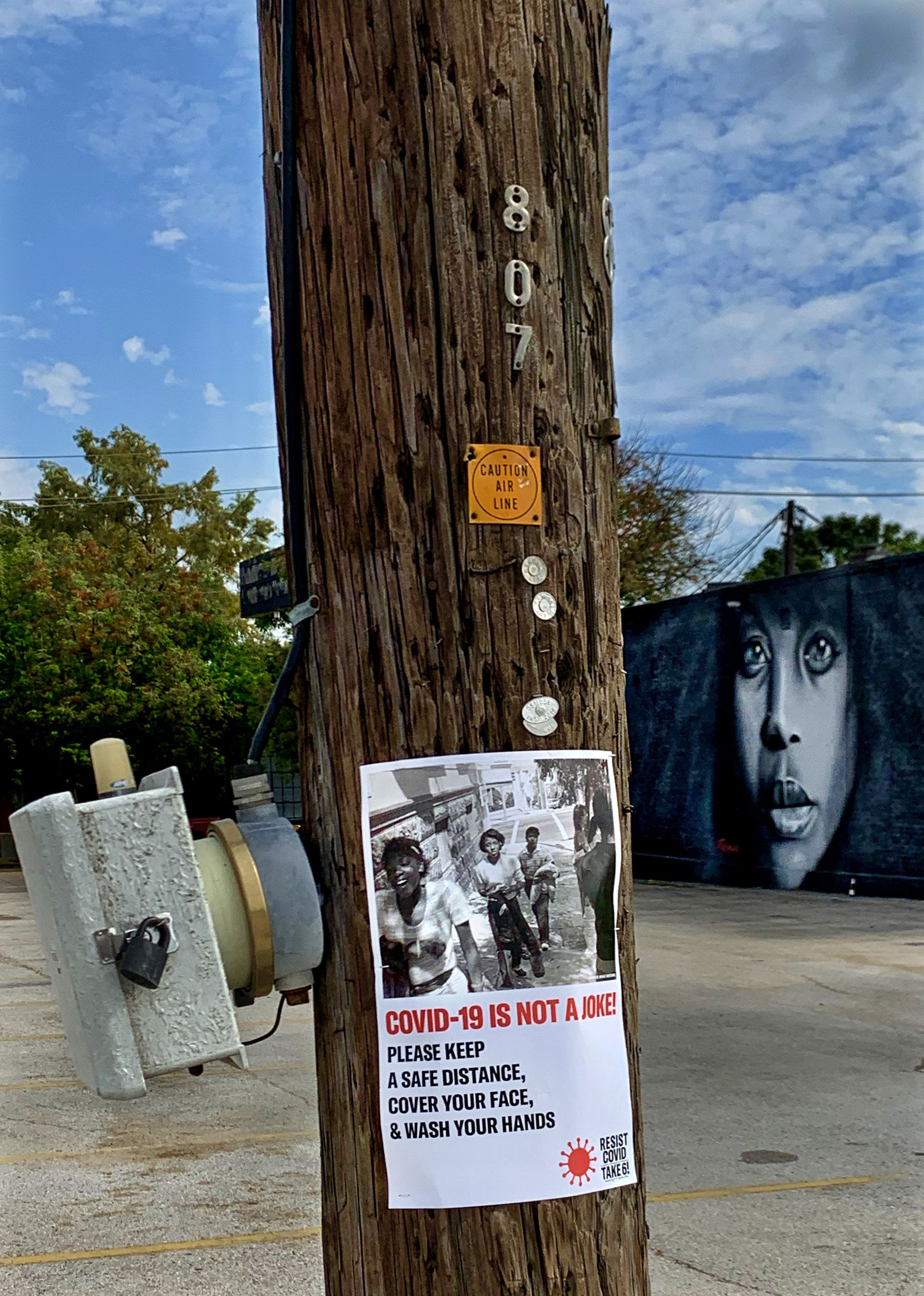 "A poster for the ""RESIST COVID/TAKE 6!"" public art campaign by artist Carrie Mae Weems calls attention to coronavirus safety measures in Deep Ellum."
