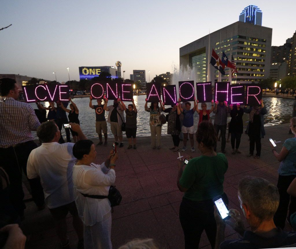 Members of the North Texas Light Brigage hold up a sign during a candlelight vigil hosted by the Dallas Police Association at Dallas City hall in Dallas, TX July 11, 2016. (Nathan Hunsinger/The Dallas Morning News)