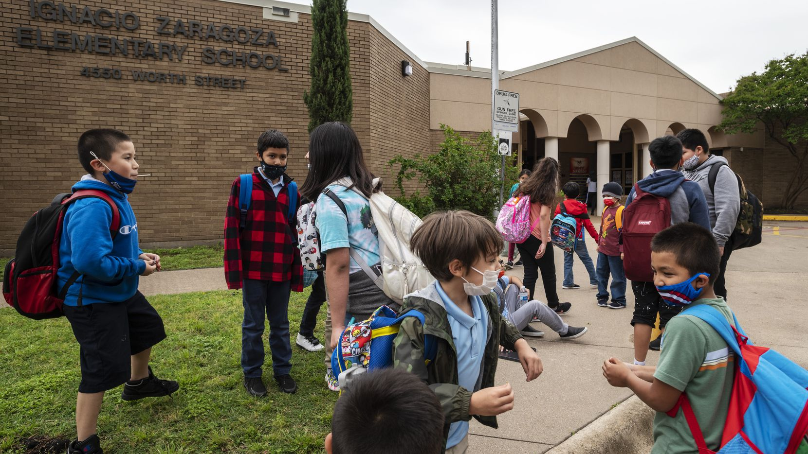 A group of students wearing face masks play outside of Ignacio Zaragoza Elementary School as they wait to be picked-up from school, on Tuesday, May 18, 2021 in Dallas. Governor Abbott issued an executive order prohibiting mask mandates by local governments including schools. The DISD mask requirement continues until June 4th.