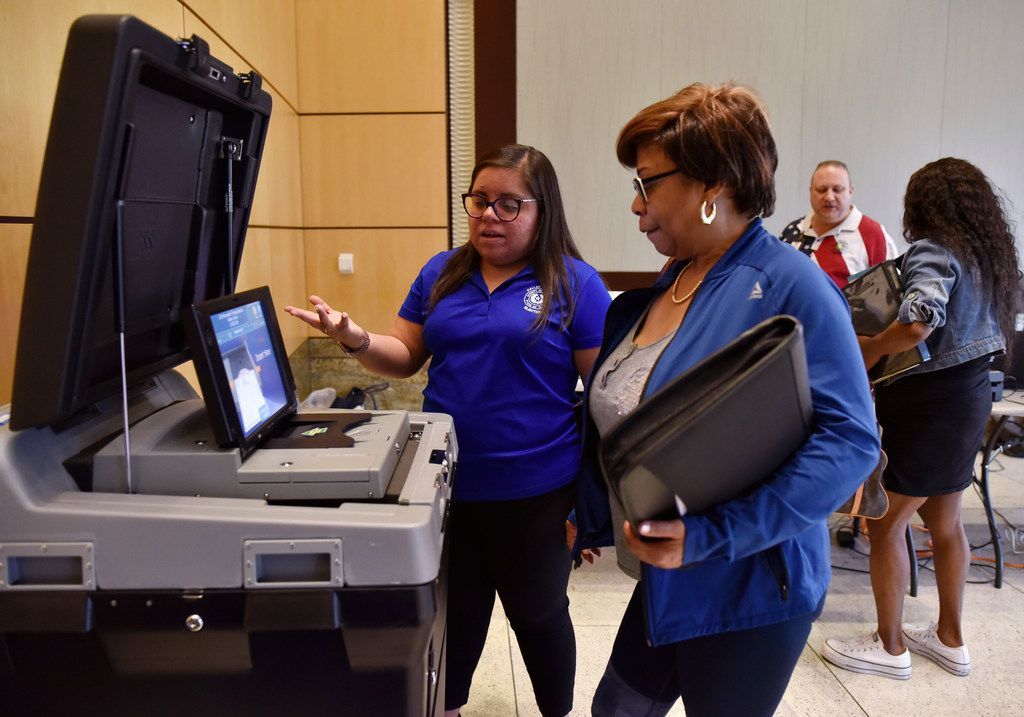 Laura Varela, left, a bilingual coordinator for Dallas County Elections, explains to Constancia Shaw how to scan her printed ballot during a demonstration of the new equipment for elections, Sept. 25, 2019 at City Hall in Mesquite. Starting this Fall, Dallas voters will use the new equipment as well as visit voter centers to cast their ballot and not the precincts they're used to. Ben Torres/Special Contributor