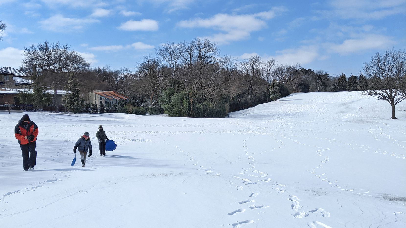 Dr. Fernan Rodriguez, his son Luca Rodriguez (center) and Will Kemp take advantage the snowy conditions to use their sleds on the third fairway at Stevens Park Golf Course in Dallas on Monday, Feb. 15, 2021.  Freezing conditions may end up causing damage to golf courses throughout North Texas.