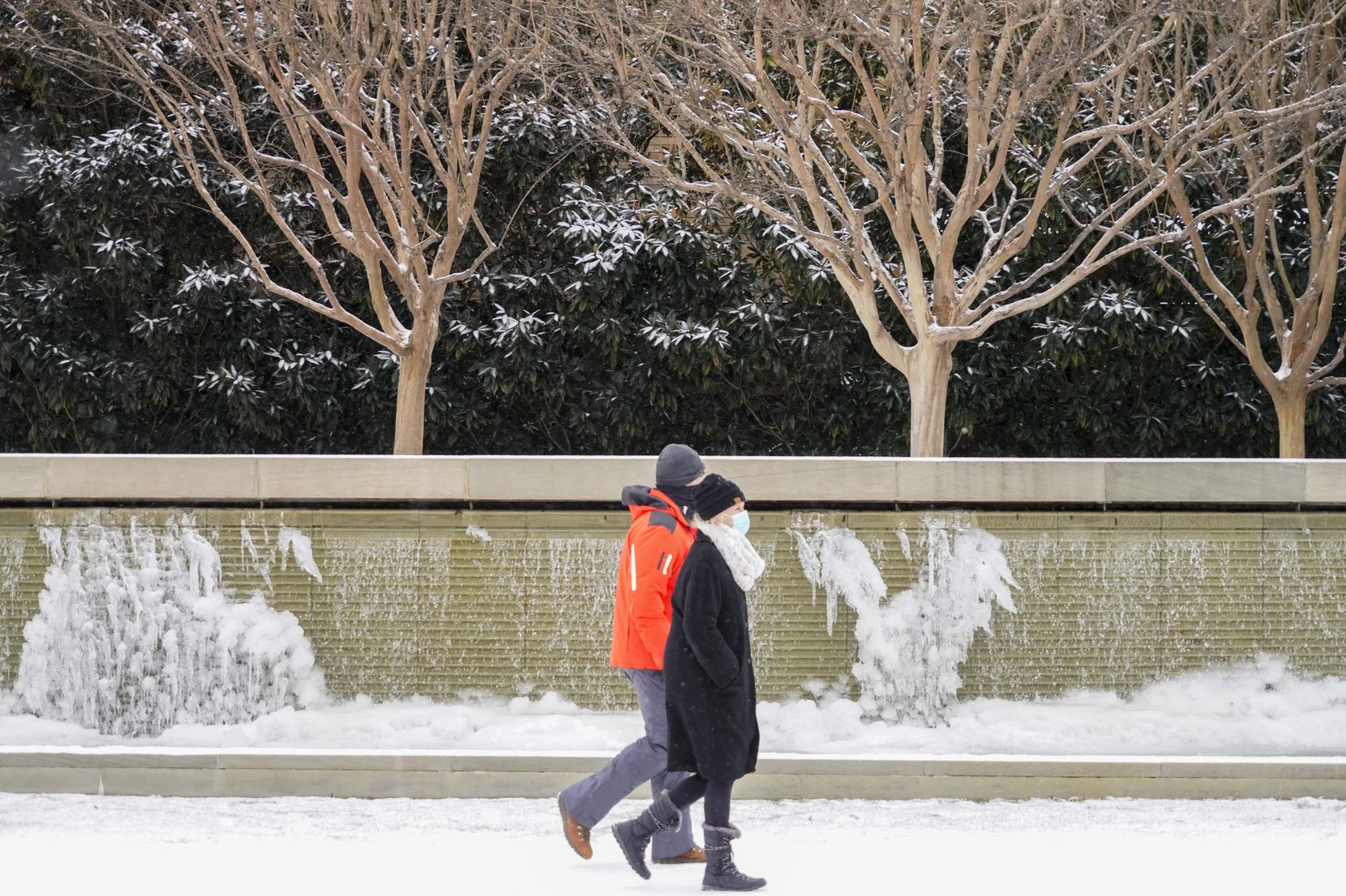 People walk past frozen fountains on Hillcrest near Lovers lane as a winter storm brings snow and freezing temperatures to North Texas on Sunday, Feb. 14, 2021, in University Park.  A winter storm watch has been issued for all of North Texas, including Dallas, Denton, Collin and Tarrant counties and will be in effect from late Saturday through Monday afternoon.