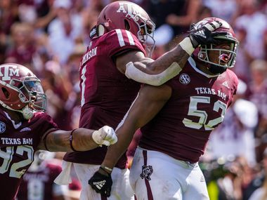 FILE - Texas A&M defensive lineman Justin Madubuike (52) celebrates with Buddy Johnson (1) and Jayden Peevy (92) after a stop in the second quarter of a game against Auburn at Kyle Field on Saturday, Sept. 21, 2019, in College Station.