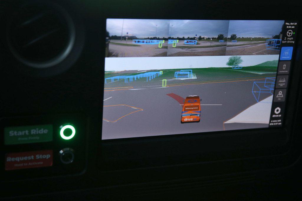 A display inside a Drive.ai self-driving vehicle shows what the vehicle sees. Pedestrians are green blocks, and parked cars are blue.