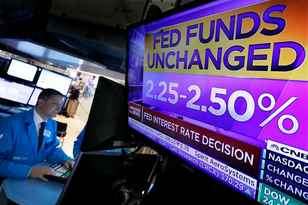 Specialist Jeffrey Berger works at his post as a television screen on the floor of the New York Stock Exchange shows the rate decision of the Federal Reserve, Wednesday, Jan. 30, 2019.