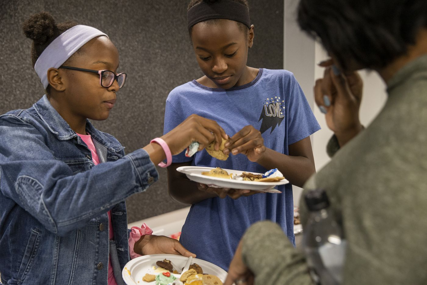 Kids' Choice category judges and sisters Sanaya Bryant (left) and Carmen Bryant, ages 12, taste cookies during the 24th annual Holiday Cookie Contest hosted by The Dallas Morning News.