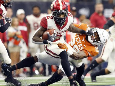 FILE - Oklahoma wide receiver CeeDee Lamb (2) stiff-arms Texas defensive back Josh Thompson (29) on a punt return during the Big 12 Championship at AT&T Stadium in Arlington on Saturday, Dec. 1, 2018.