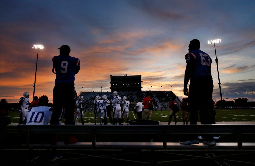 As the sun sets at Beverly D. Humphrey Tiger Stadium in Lancaster Texas, injured Duncanville football players watch their game against Lancaster from atop the bench, Friday, August 30, 2019. (Tom Fox/The Dallas Morning News)