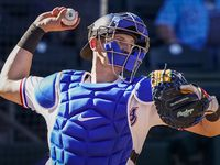 Texas Rangers catcher Sam Huff makes a throw to second base during the eighth inning of a spring training game against the Kansas City Royals at Surprise Stadium on Tuesday, Feb. 25, 2020, in Surprise, Ariz.