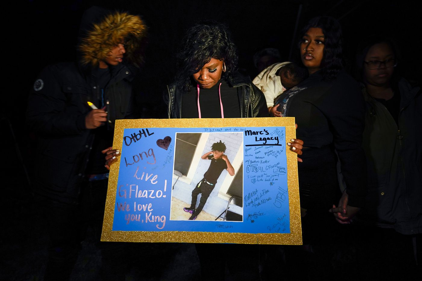 """Monique Mitchell holds a photograph of her son Marc """"Flea"""" Strickland, an 18-year-old victim of a shooting at Dallas ISD basketball game, during a vigil at Bushman Park on Sunday, Jan. 19, 2020."""