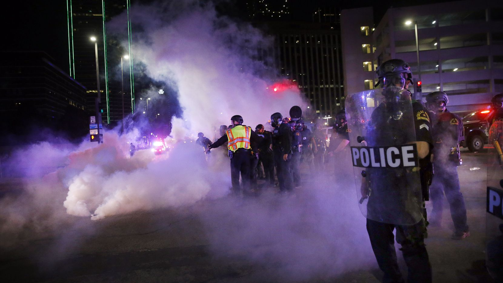"Dallas police tactical officers fire rounds of tear gas at protesters in downtown Dallas. At least two Dallas officers had in the past joked about using chemical agents to quell crowds. One called it a ""participation trophy."""