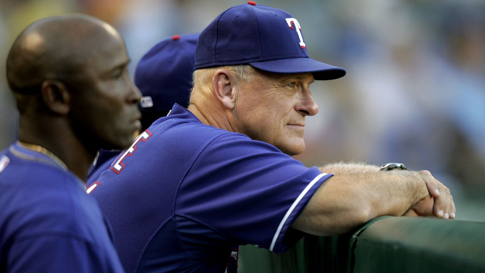 Texas Rangers first base coach Gary Pettis, left, and bench coach Art Howe, center, watch the action from the dugout rail against the Seattle Mariners at Rangers Ballpark in Arlington Monday, July 28, 2008.