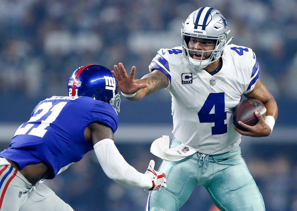 Dallas Cowboys quarterback Dak Prescott (4)gives a stiff arm to New York Giants defensive back Landon Collins (21) as he kept the ball and ran during the first quarter at AT&T Stadium in Arlington, Texas, Sunday, September 16, 2018.