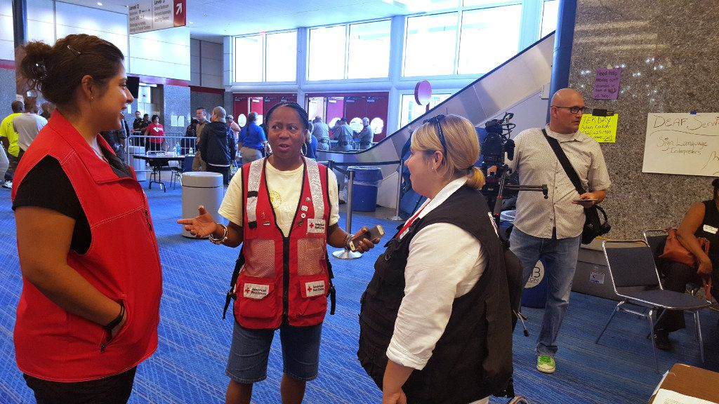 Vic Parker, a Red Cross volunteer from Delaware who's managing the Harvey refugee center at the George R. Brown Convention Center in downtown Houston, fields questions from other volunteers Thursday. The center had about 2,500 displaced residents under its roof by noonThursdsy, down from a high of about 10,000 earlier in the week.