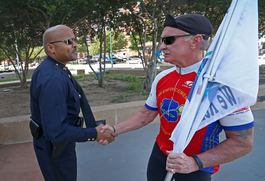 John Lawton (left), an assistant chief who's now a major, shook hands with a retired police officer riding in a memorial bike ride in April.
