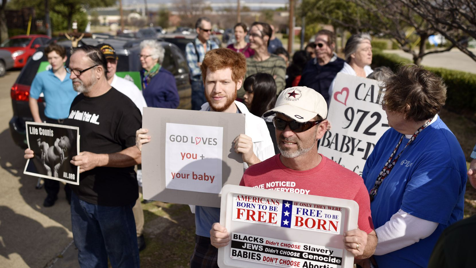 Abortion opponents Ethan Moon, 24, left, of Dallas, and Bobby Pope, 50, of Forney, hold their signs while quietly standing along a sidewalk during a protests outside of the Planned Parenthood, South Dallas Surgical Health Services Center, Saturday morning, Feb. 11, 2017 in Dallas.