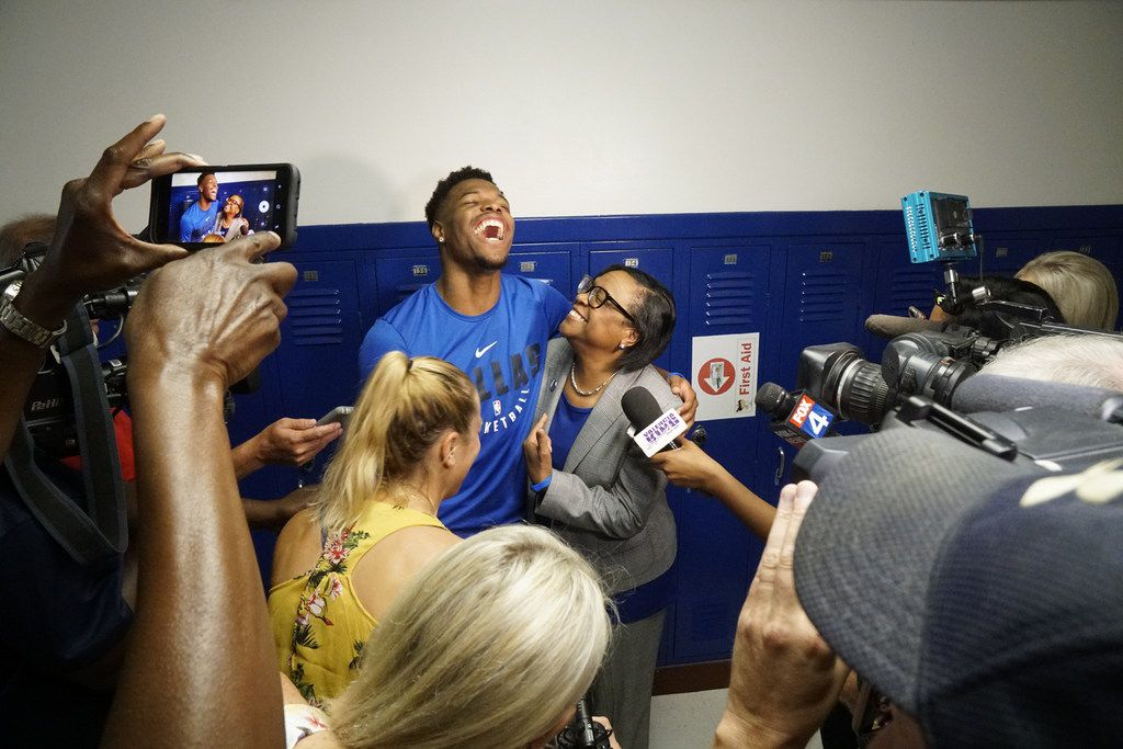 Dallas Mavericks point guard Dennis Smith Jr. and CEO Cynthia Marshall speak to the media at Sidney Lanier Expressive Arts Vanguard in Dallas on Aug. 20, 2018. The Mavericks celebrated the new school year with the students by teaching a basketball clinic, giving every kid an activity tracker and donating balls to the school.