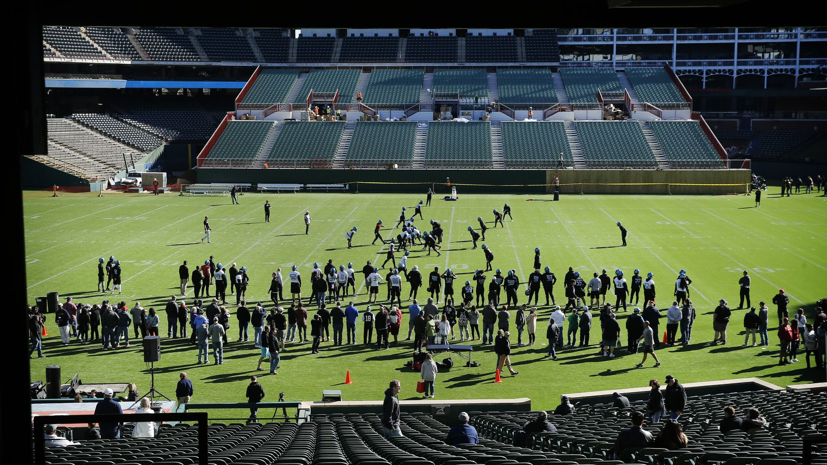The XFL's Dallas Renegades football team practices before fans on the newly constructed football field at Globe Life Park in Arlington, Texas, Saturday, February 1, 2020. Stands (pictured) are being constructed in left field of the old baseball stadium. Their season starts February 9.