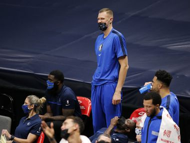 Injured Dallas Mavericks forward Kristaps Porzingis laughs along with his teammates during their preseason game against the Minnesota Timberwolves at the American Airlines Center in Dallas, Thursday, December 17, 2020.