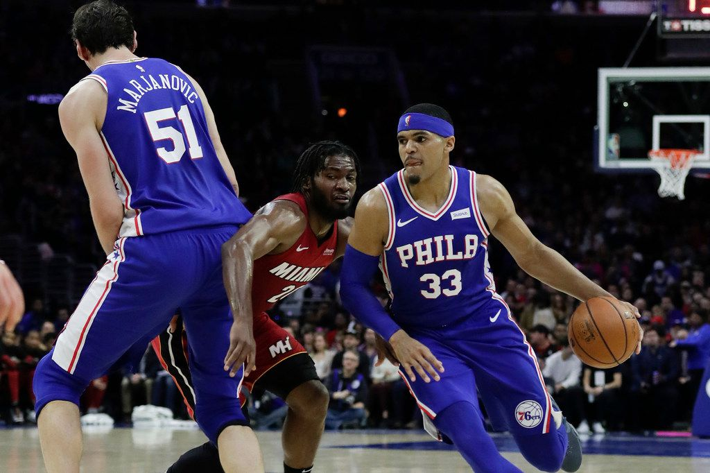 The Philadelphia 76ers' Tobias Harris (33) drives off a screen from teammate Boban Marjanovic (51) against the Miami Heat's Justise Winslow at the Wells Fargo Center in Philadelphia. (Yong Kim/Philadelphia Daily News/TNS)