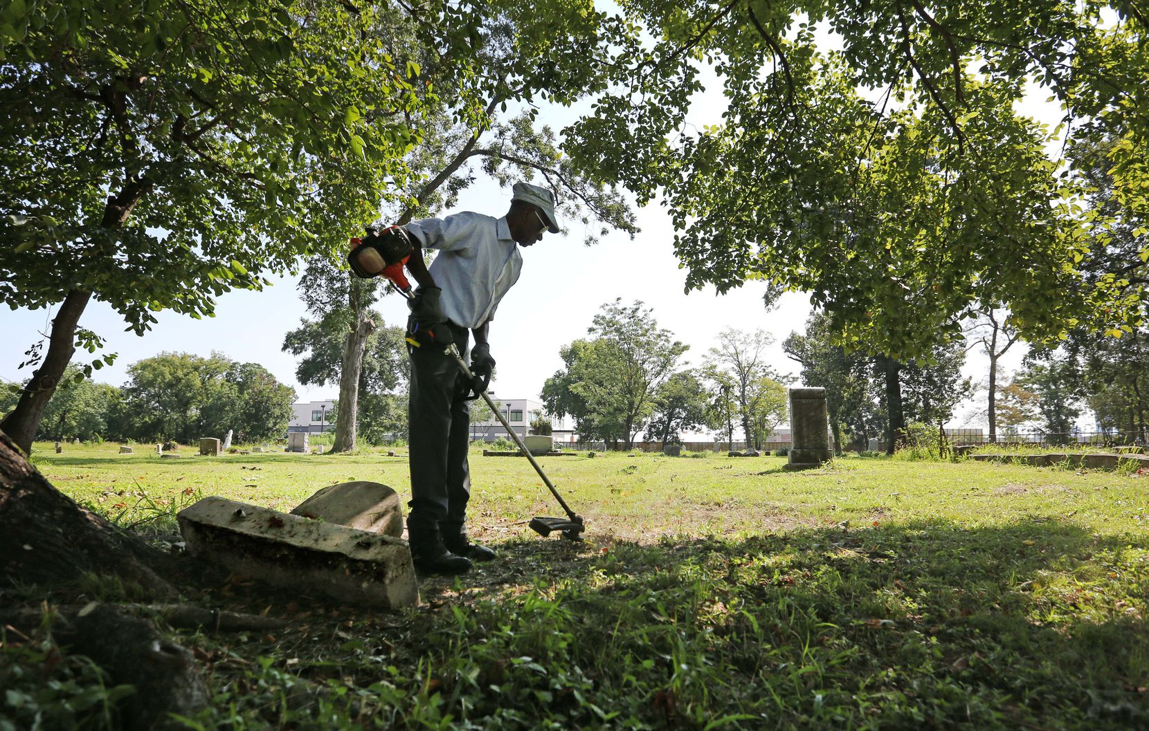 Charles Cook, groundskeeper at Olivewood Cemetery in Houston, works at cutting the grass around a toppled headstone on Sunday, September 10, 2017.