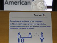 Signs reminding people to keep their distance at an American Airlines gate in terminal C at DFW International Airport on Wednesday, April 8, 2020. The coronavirus pandemic has made an impact on the travel industry. (Vernon Bryant/The Dallas Morning News)
