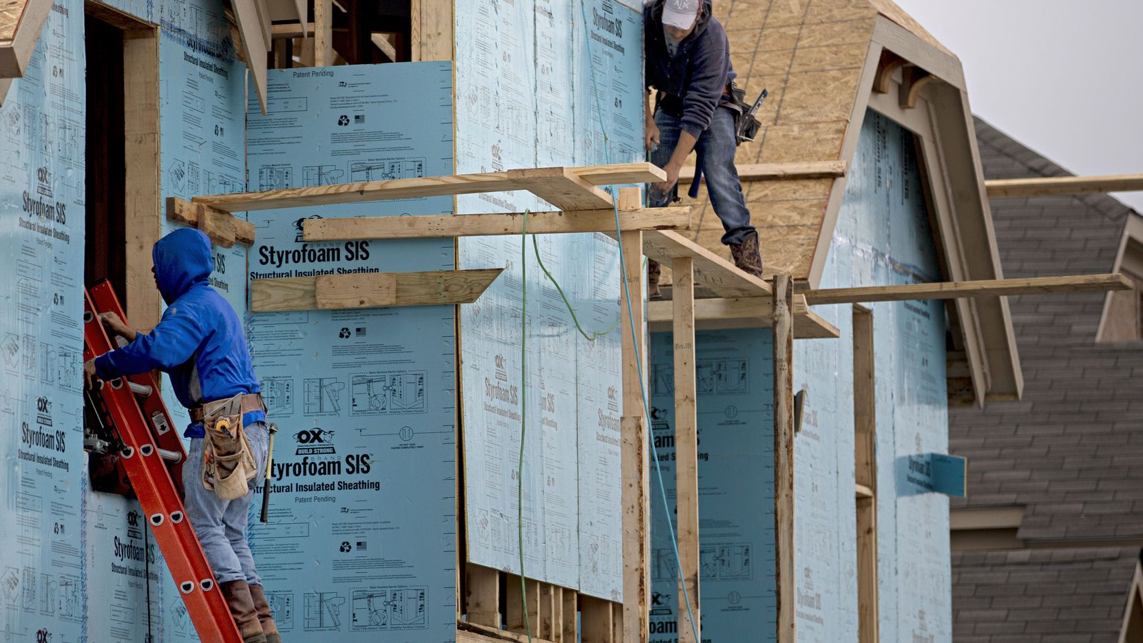 Workers build a house in the Richwoods: Landon Homes subdivision  in Frisco. A shortage of labor has added at least two months to most building jobs.