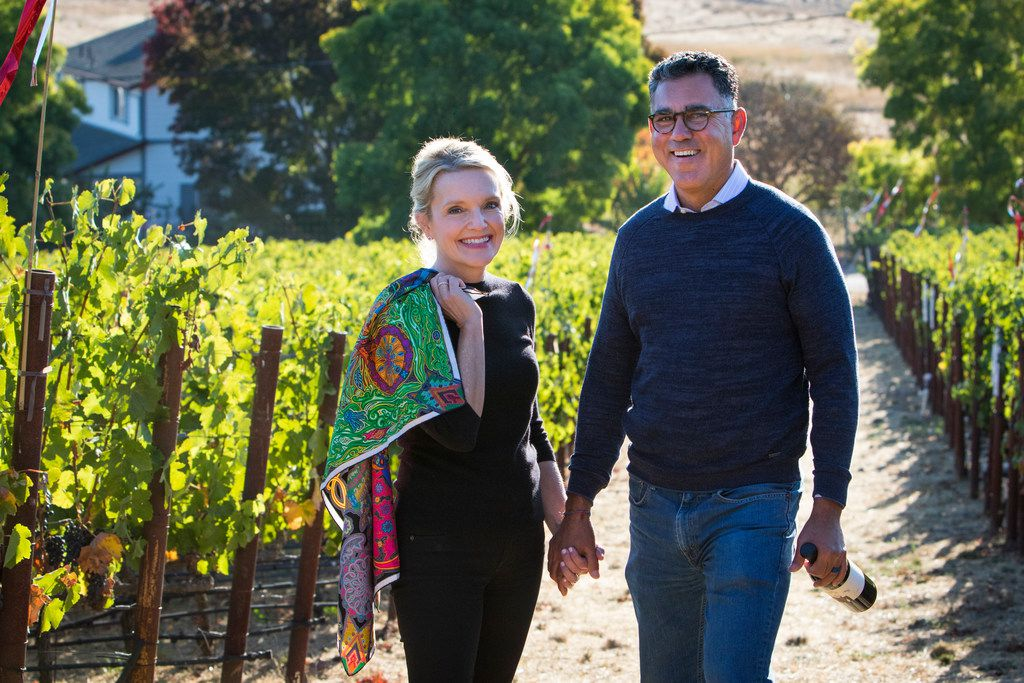 Margaret and Joe Valenzuela stroll through one of Napa Valley's many vineyards. She is wearing one of her trademark scarfs, which grace the new labels of their Rubia wine like the bottle he carries in his hand.