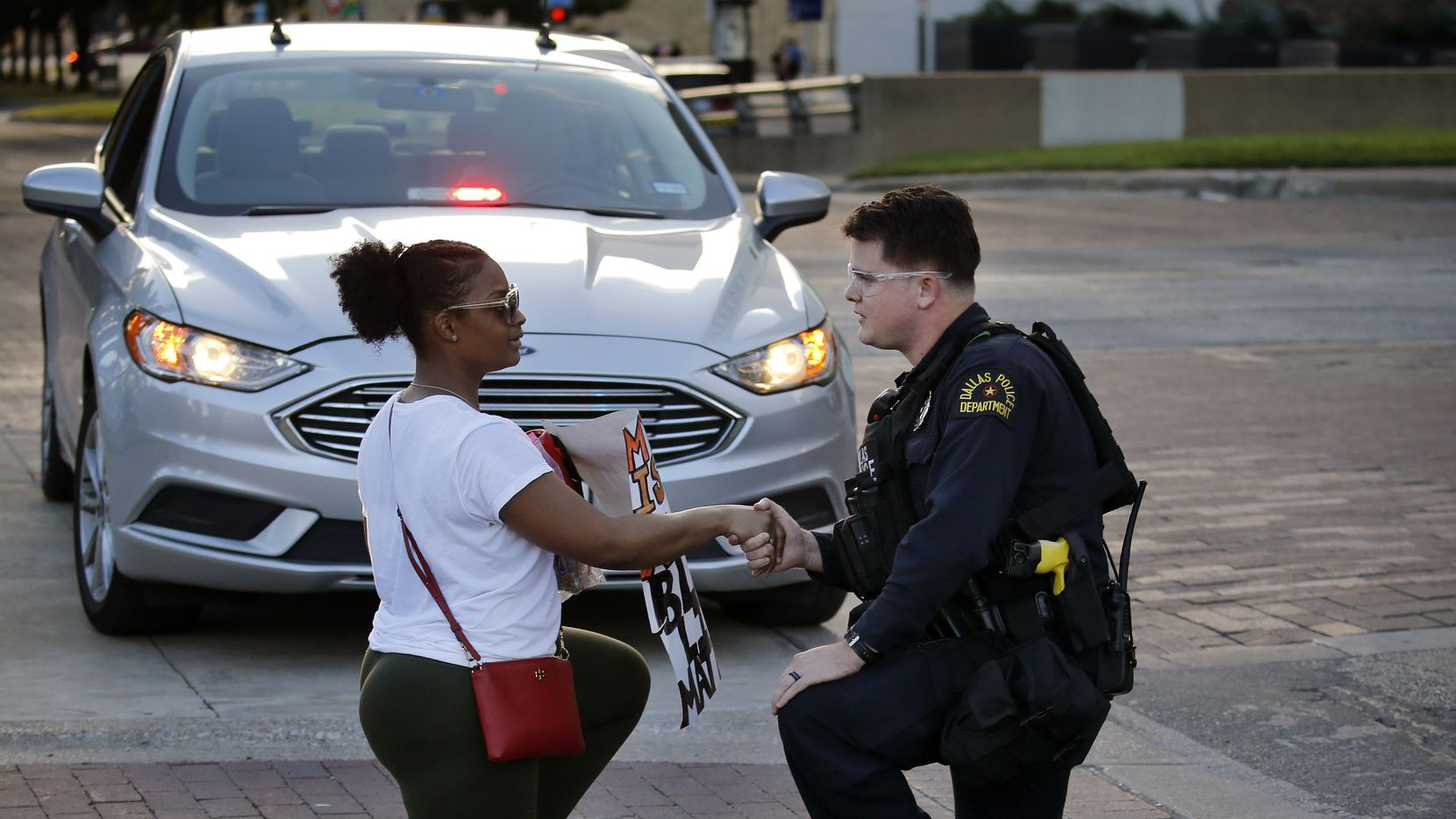 Protestor Slowanna Delavontae (left), who lives in the South Dallas area of Dallas, shakes hands with Dallas Police patrol officer Caleb Morkert after the two took a knee following a march back to Dallas City Hall, Thursday, June 4, 2020. Morkert listened to the grievances of Delavontae as curfew neared. The protestors were marching in response to the in-custody death of George Floyd in Minneapolis.