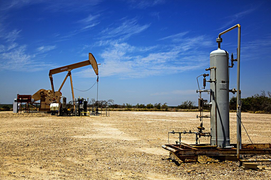 FILE photo shows an oil pumpjack working in the background by natural gas machinery in Webb County, Texas. (G.J. McCarthy/The Dallas Morning News)
