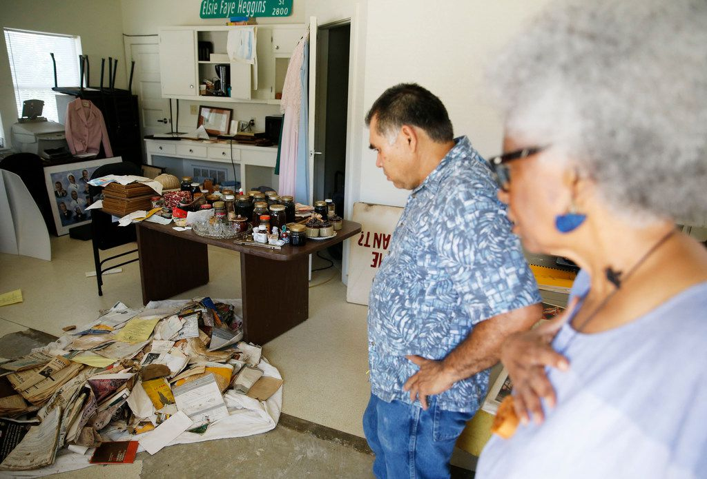 City worker Oscar Mancia, left, and Marilyn Clark look at some of Craft's belongings rescued from the house after this weekend's flood.