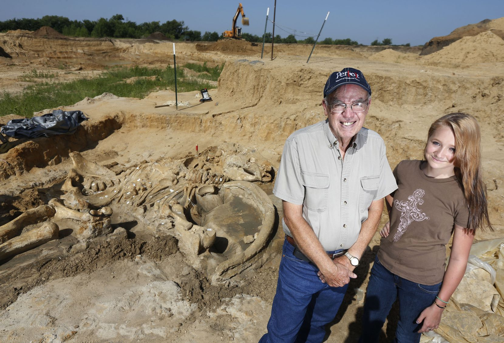 Wayne McEwen poses with granddaugther Halee Beasley, 13, at the site where he uncovered a well-preserved mammoth skeleton in his Ellis County gravel pit. He is donating the skeleton to the Perot Museum of Nature and Science in Dallas.