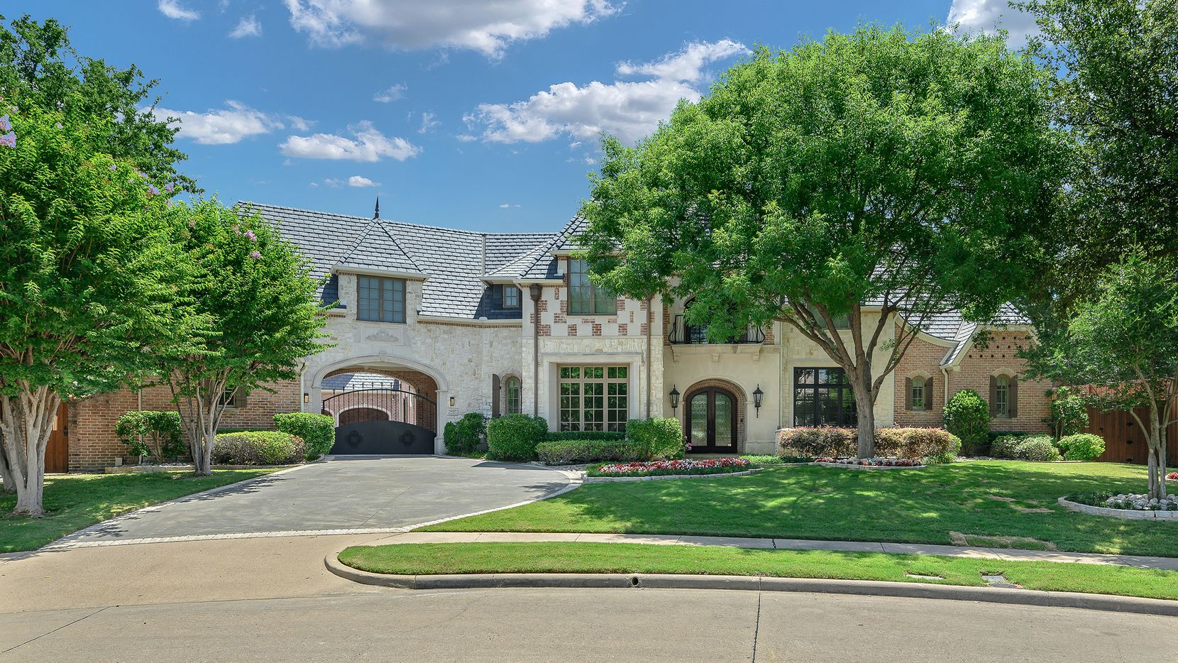 The estate at 4008 Wishing Well Lane in Dallas is listed at $1,699,000. Amenities include a pool and spa, gated porte-cochere with a basketball area and Tesla charging station.