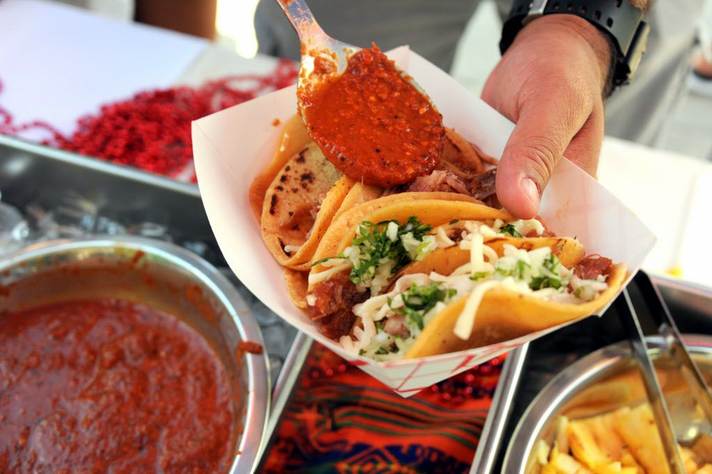 Barbacoa tacos are served with hot sauce. Sunday is National Taco Day.