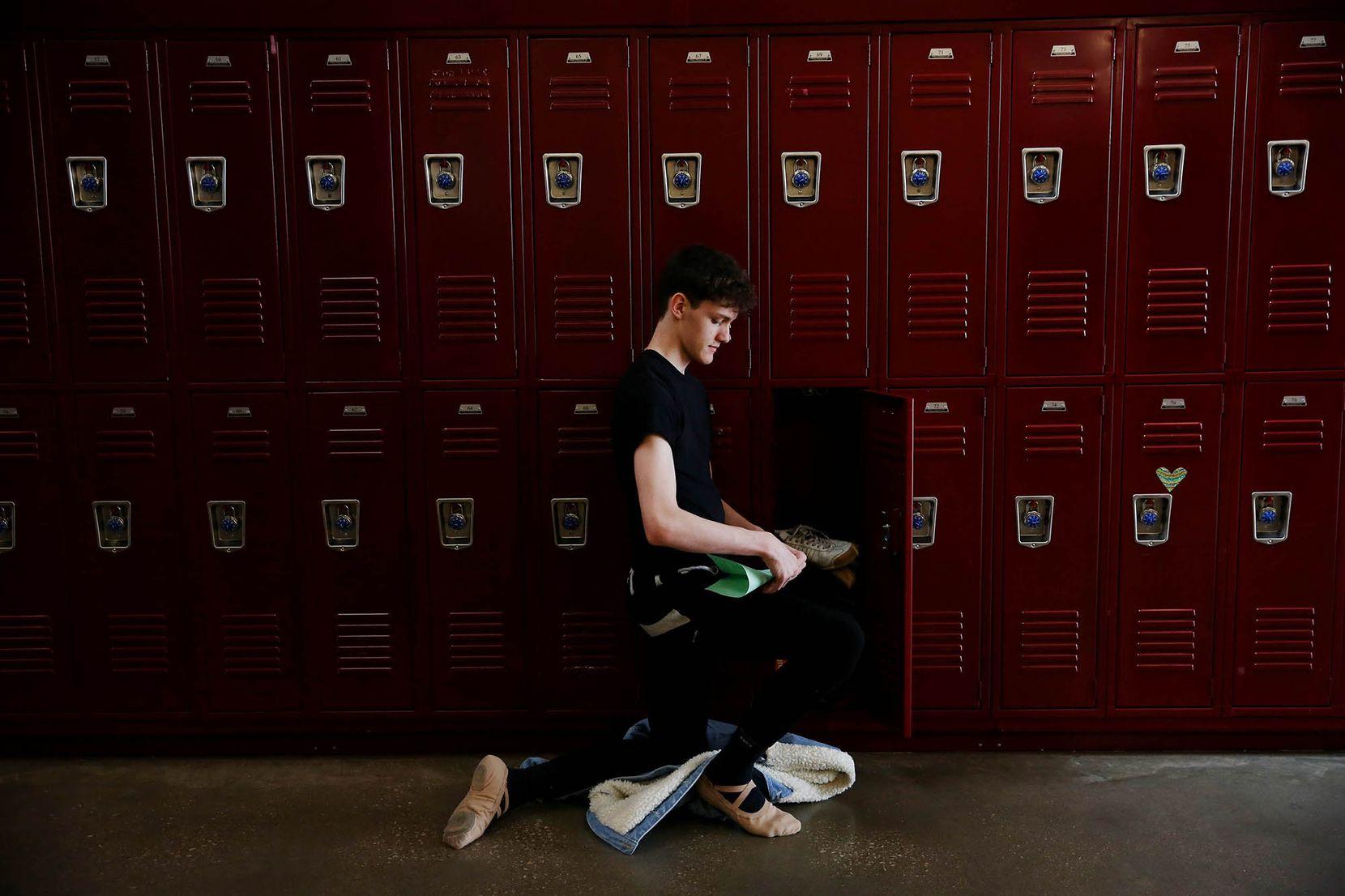 Dancer Lucas Dyson, a junior, kneels by his locker in-between classes.