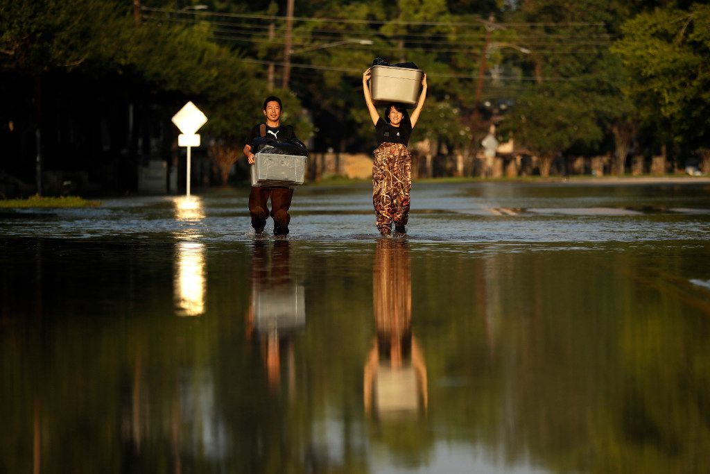 Mariko Shimmi, right, helps carry items out of the home of Ken Tani in a neighborhood still flooded from Harvey on Monday in Houston. Some neighborhoods around Houston remain flooded and thousands of people have been displaced by torrential rains and catastrophic flooding since Harvey slammed into Southeast Texas last week. (AP Photo/Gregory Bull)