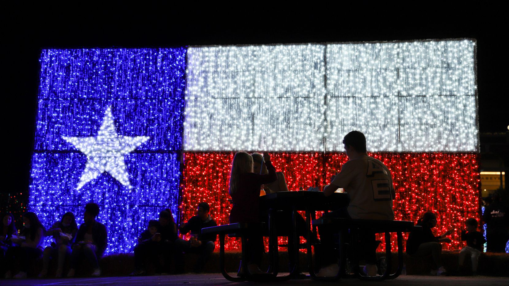 Guests enjoy food and drink in front of a Texas flag lighted sculpture at Luminova Holidays at Globe Life Field in Arlington, Nov. 21, 2020.