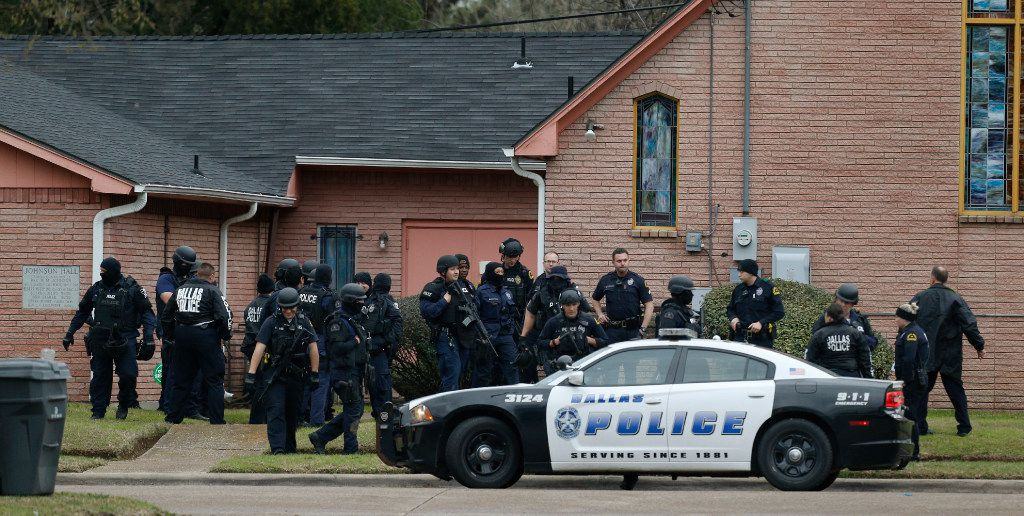 Dallas Police and SWAT gather around Olivet Missionary Baptist Church after a person who barricaded him or herself inside a home after serving a warrant in the 2700 block of Lenway in Dallas on February 14, 2017.  (Nathan Hunsinger/The Dallas Morning News)